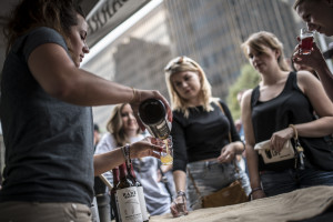 An image of a young woman bartender pouring a small glass of beer for two other young women patrons at the Beer Fest