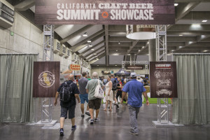 an image of some Craft Beer Summit goers walking through Cal Expo with a sign above them that reads 'California Craft Beer Summit Showcase'
