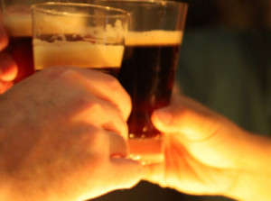 a close up image of two people clinking their beer glasses together in a toast